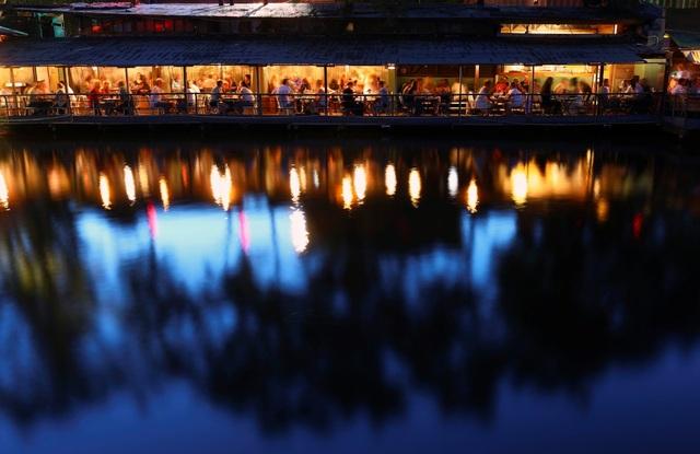 Du khách tới thưởng thức đồ uống với bữa tối sau một đêm tiệc tùng bên dòng kênh Flutgraben. Nơi này được phát triển thành khu giải trí về đêm.