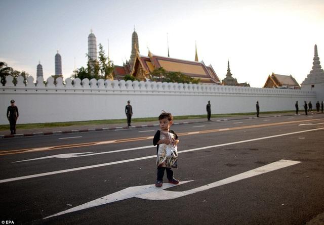 Một bé trai người Thái ôm bức hình về các thành viên Hoàng gia
