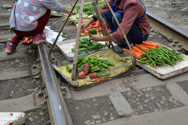 Các mẹt hàng rau củ được bày bán ngay trên đường ray