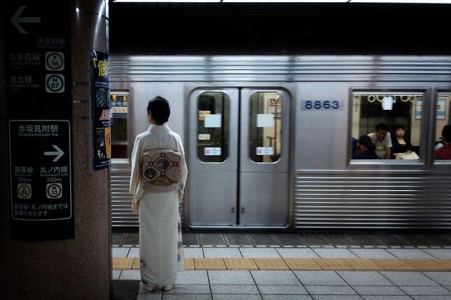 Một người phụ nữ mặc kimono truyền thống đứng chờ tàu điện.