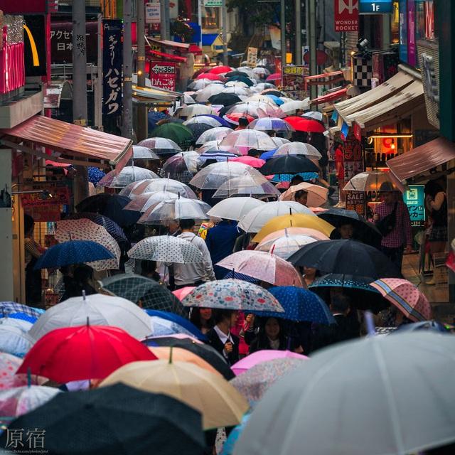 Cảnh chen chúc trên con phố đông người với những chiếc ô nối tiếp nhau trong ngày mưa.