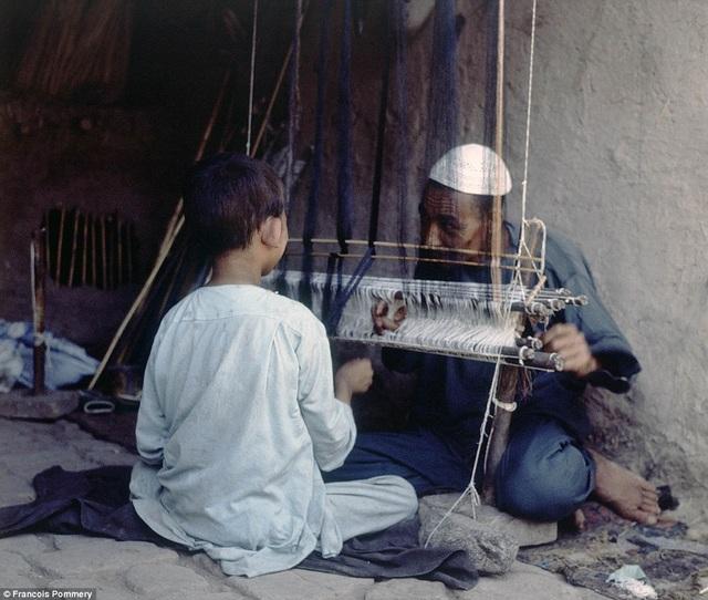 Giữ gìn nghề truyền thống từ thế hệ này qua thế hệ khác. Trong hình là cảnh một người đàn ông đang hướng dẫn cậu bé cách dùng khung cửi.