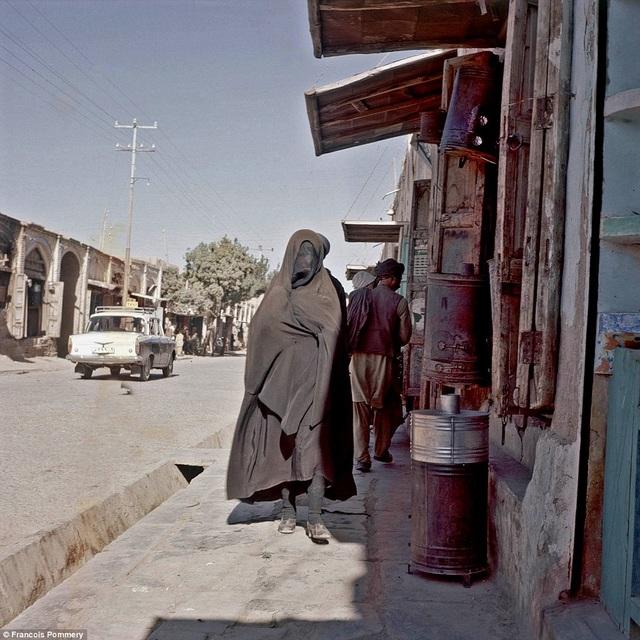 Một người phụ nữ trùm kín trang phục đen đi trên đường ở Heart. Ảnh chụp năm 1974.