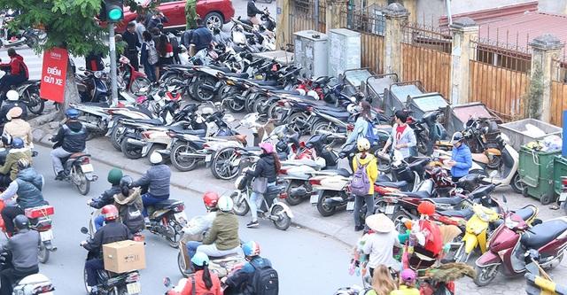 Một cửa hàng quần áo trên phố Chùa Bộc có số lượng khách hàng quá đông khiến bãi để xe cho khách trước cửa quá tải. Khách hàng tới mua đồ phải để xe kín cả vỉa hè phía bên kia đường.