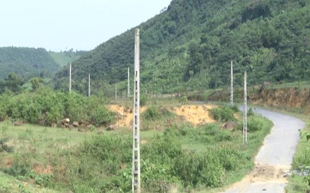 Hàng chục cột điện đứng trơ trọi và con đường làm vào khu tái định cư cỏ mọc um tùm hai bên.
