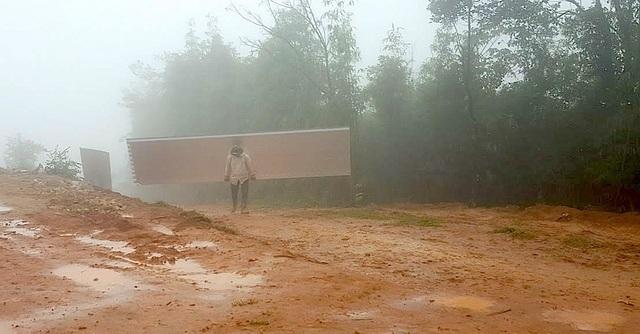 Một người đàn ông vất vả gùi tôn lên điểm trường mới.