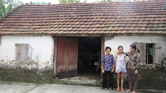 Ba mẹ con bà cháu bên căn nhà cũ nát.