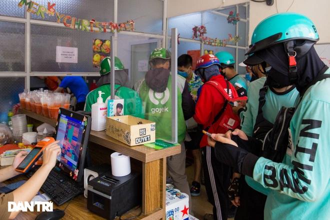 Cảnh shipper chen chúc trong hàng quán ở Hà Nội để lấy đồ ăn giao cho khách - 1