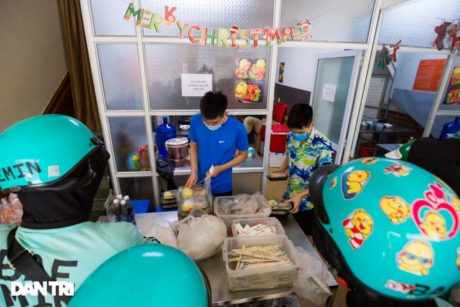 Cảnh shipper chen chúc trong hàng quán ở Hà Nội để lấy đồ ăn giao cho khách - 7