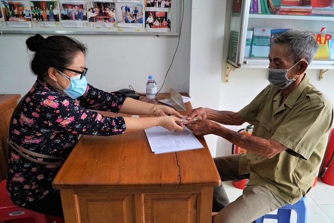 Cán bộ phòng LĐ-TB&XH trao tiền hỗ trợ tới ông Trần Văn Chợ, khu vực 4, phường An Bình, Ninh Kiều, Cần Thơ.