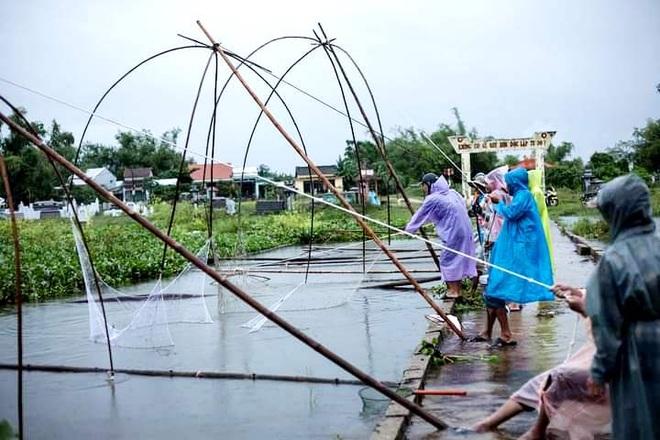 Người dân giăng lưới bắt cá sau mưa lớn - 1