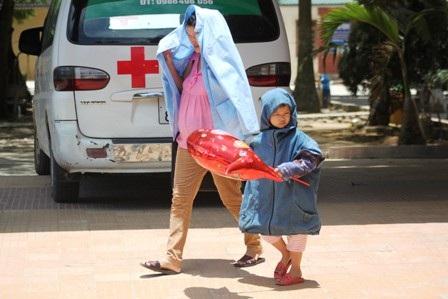Phụ huynh vất vả đưa con đi viện trong nắng nóng