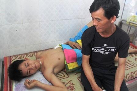Em Nguyễn Văn Hiệp (SN 1995, học sinh lớp 12D3, trường THPT Anh Sơn I) đang được bố chăm sóc.