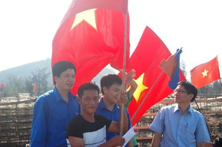 Anh Nguyễn Đình Hùng - Bí thư tỉnh Đoàn Nghệ An trao cờ và quà cho ngư dân