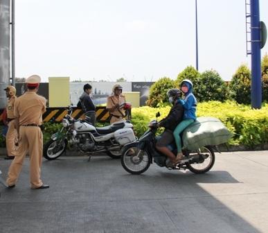 Xe máy của người thanh niên chở đầy hàng khiến người ngồi sau phải ngồi cheo leo hết sức nguy hiểm,