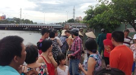 Rất đông người hiếu kỳ đứng dọc 2 bên kênh và trên cầu theo dõi vụ việc.