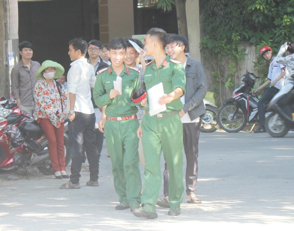 Hai bố con Hiền lên đường đến điểm thi cùng với mấy chai nước treo trước xe. (Ảnh: Hoàng Lam)