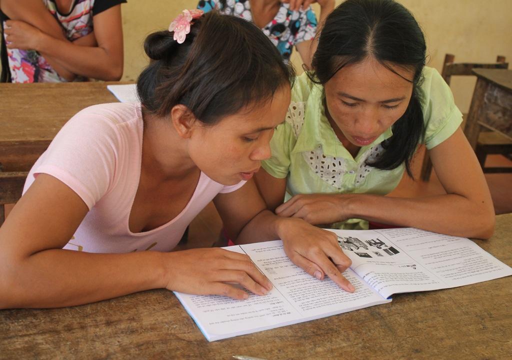 Học viên lớp xóa mù ở bản Mọi (Lục Dạ, Con Cuông, Nghệ An) giúp nhau học bài.