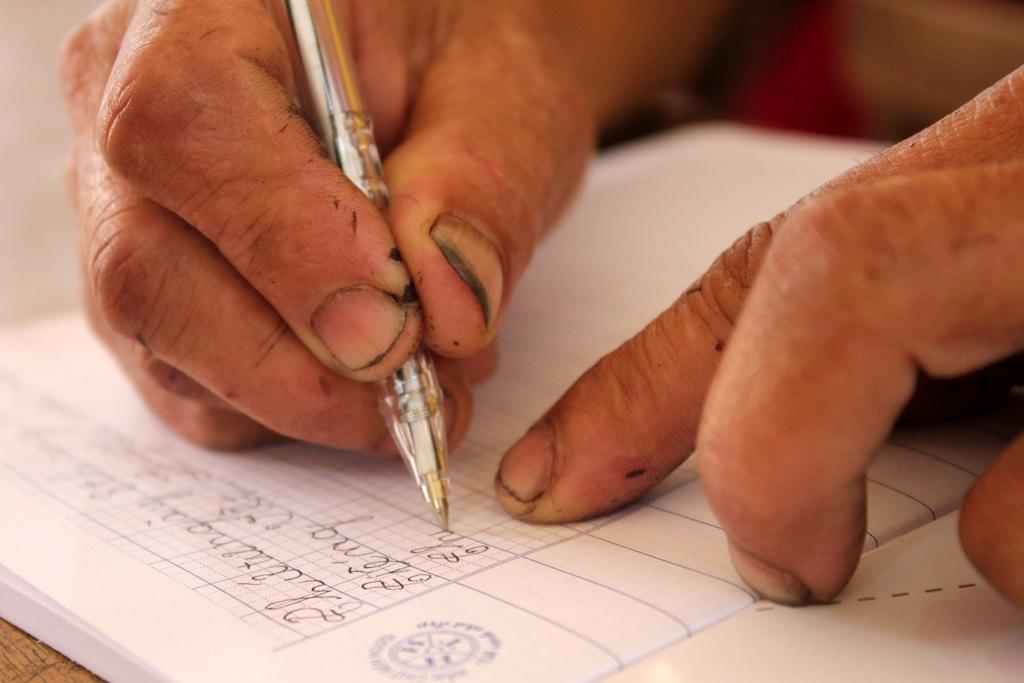 Những bàn tay chai sạn, nứt nẻ cần mẫn đưa từng nét bút.