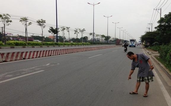 Một người dân đang chỉ lại hiện trường nơi xảy ra vụ cướp xe SH của trung úy CSGT trên Xa lộ Hà Nội
