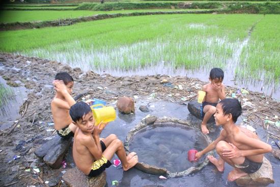 """Trẻ con thôn Hà Bắc thích thú khi """"tắm nước nóng giữa đồng""""."""