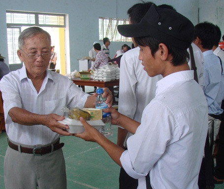 Thành viên trong đoàn từ thiện của Tịnh xã Ngọc Quảng trao bữa cơm tới thí sinh.