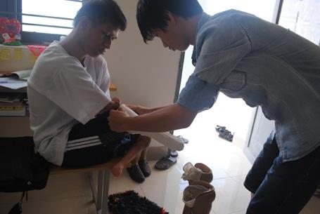 Dj Ruêng được một người bạn trong phòng giúp mang chân giả để em có thể đi bộ đến lớp.