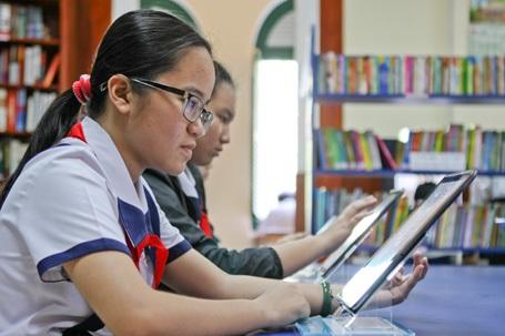 Các em học sinh Trần Đại Nghĩa đang chăm chú tra cứu thông tin bằng Galaxy Tab trong thư viện.