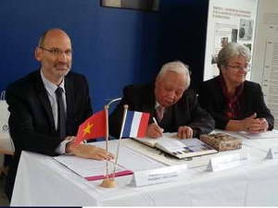 Giáo sư-viện sĩ Nguyễn Văn Hiệu (giữa) ký Sổ vàng của ĐH Sư phạm Cachan. (Ảnh: Tiến Nhất/Vietnam+)