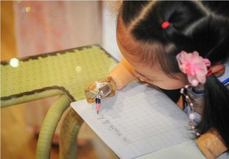 Linh Chi viết chữ trên đôi bàn tay giả.