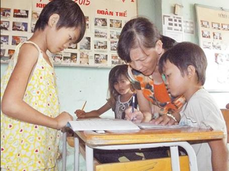 Bà giáo Năm dạy các em tập đọc.