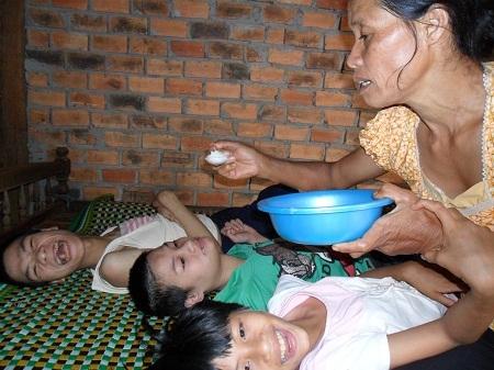 Ba đứa con tật nguyền của bà Phạm Thị Vinh nằm một chỗ trên giường từ khi sinh ra cho đến nay.