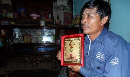 Anh Lê Văn Hiệu bên bức ảnh Bác Hồdo Phó Chủ tịch nước Nguyễn Thị Doan tặng.