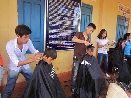 """Cắt tóc cho trẻ em trong """"Ngày hội Nhân ái vì sức khỏe cộng đồng""""."""