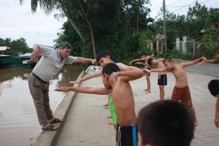 Trước khi cho các em xuống nước bơi, thầy Sứng rất chú tâm đến công tác khởi động cho các em.