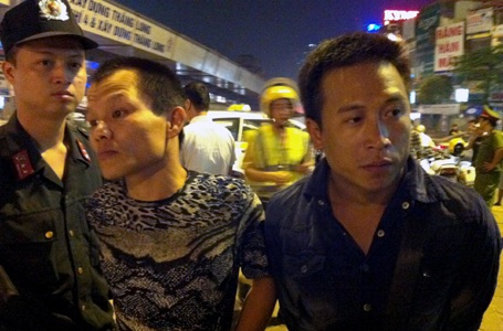 Đối tượng Bình (phải) bị cảnh sát bắt giữ.