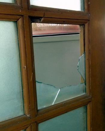 Cánh cửa nhà chị Nam bị chém vỡ kính, in vết dao sắc lẹm trên gỗ.