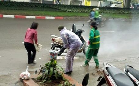 Hai người phụ nữ giúp chủ xe (áo mưa tím) dập lửa.