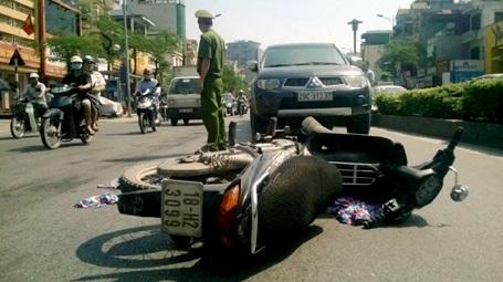 Chiếc xe máy nằm chỏng chơ giữa đường sau khi va chạm với ô tô.