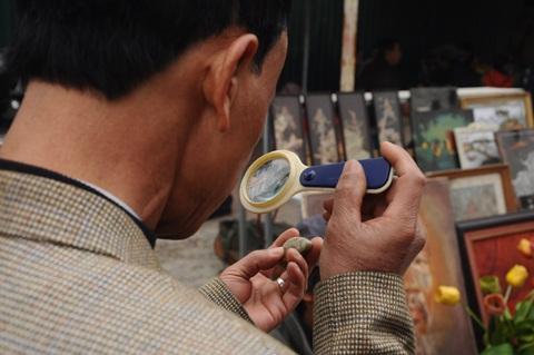Khách cầm theo kính phóng to để xem đồ cổ cho kỹ càng