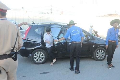 Tình nguyện viên giúp một thí sinh mở cửa xuống xe