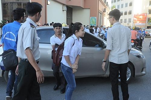 Một nữ sinh vội vã vào phòng thi sau khi xuống xe