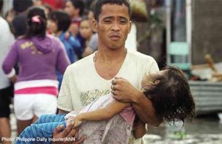 Người cha đau khổ bế con gái 6 tuổi thiệt mạng ra khỏi đống đổ nát tại Philippines.