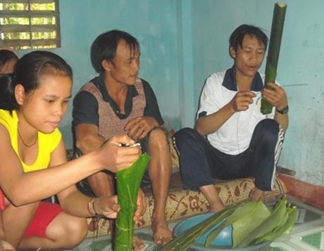 Lang (bìa phải) ngồi gói bánh trong căn nhà mới.