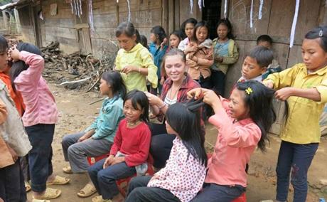 Tình nguyện viên nước ngoài đang tết tóc cho các học sinh La Hủ