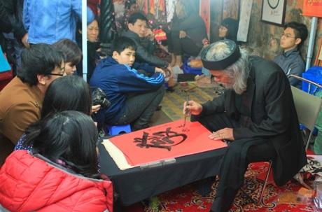 Rất đông các bạn trẻ ngồi xếp hàng chờ đến lượt xin chữ trên vỉa hè Văn Miếu