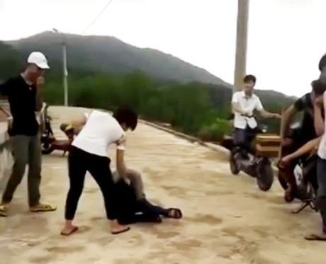 Kéo lê nạn nhân bất chấp nhiều nam thanh niên đứng ngoài xem. Ảnh cắt từ clip