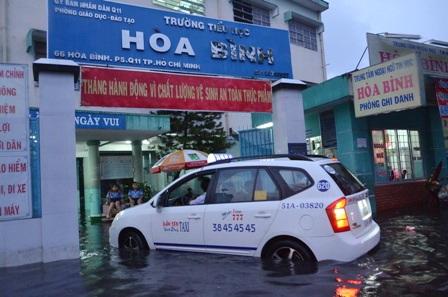 Nhiều phụ huynh phải thuê taxi để đón con vì đường ngập