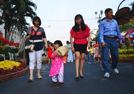 Bé gái thích thú trong trang phục áo dài được mẹ dẫn đi dạo đường hoa