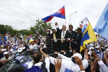 Ông Rainsy (giữa) được chào đón khi trở về Phnom Penh